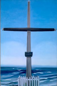 simple black and grey cross stands in front of seascape, base of cross enclosed in small fenced area with grass, a plaque/memorial placed in center of cross's base.